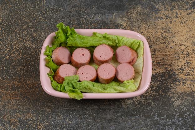 Fatias de salsichas grelhadas em uma tigela rosa.