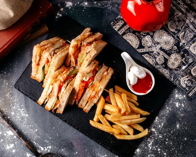 Fatias de sanduíche de vista frontal saborosas junto com batatas fritas dentro de chapa preta no chão cinza