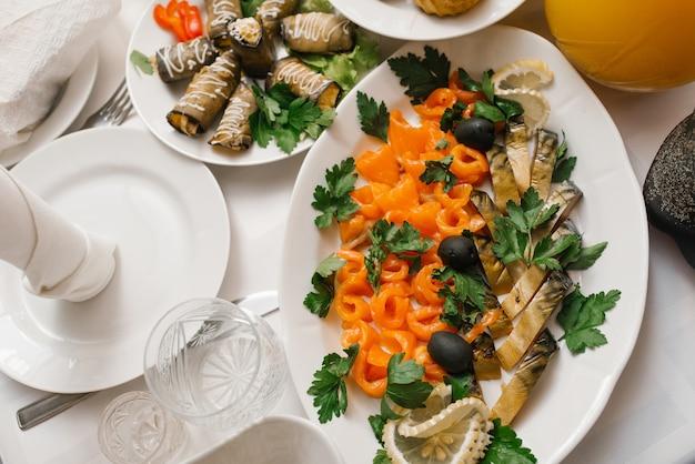 Fatias de sardenha defumadas cortadas em um prato e salmão salgado.