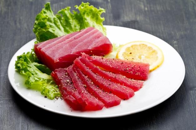 Fatias de sashimi de atum rabilho cru no prato branco em madeira est