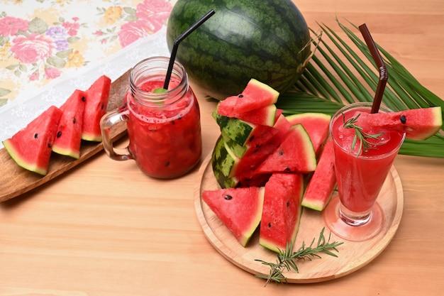 Fatias de smoothie e melancia na mesa de madeira. bebida refrescante de verão.