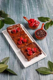 Fatias de sobremesa de bolo de brownie de chocolate com framboesas e especiarias, vista superior