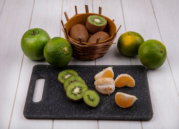 Fatias de tangerina de frente em uma tábua de cortar com kiwi em uma cesta e tangerinas verdes e uma maçã em uma parede branca