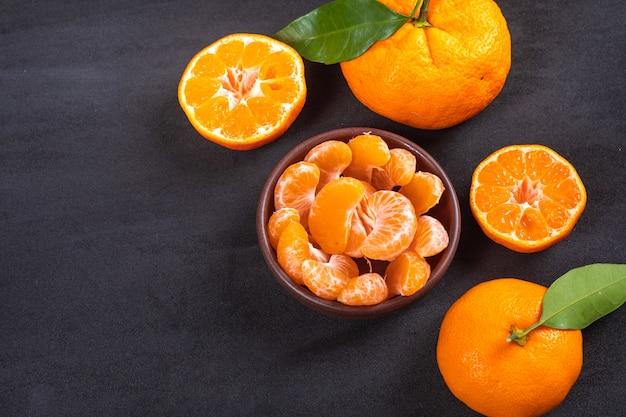 Fatias de tangerina em uma tigela de cerâmica na superfície preta
