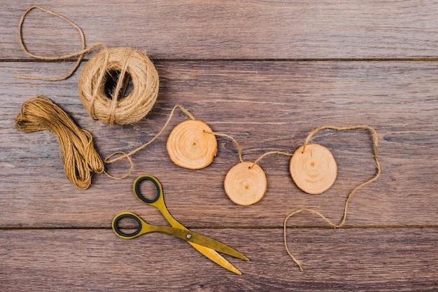 Fatias de toco de árvore com fio de juta e tesoura na mesa de madeira