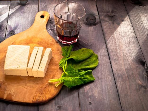 Fatias de tofu cru, espinafre e vinho