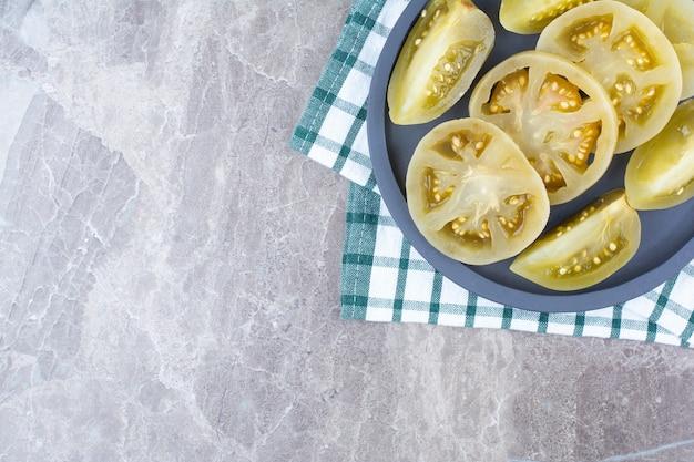 Fatias de tomate fermentado no quadro escuro com toalha de mesa.