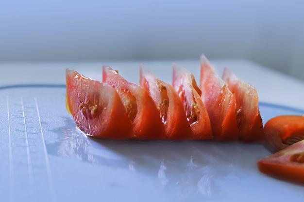 Fatias de tomate na tábua. fundo azul. conceito de fatia de tomate.