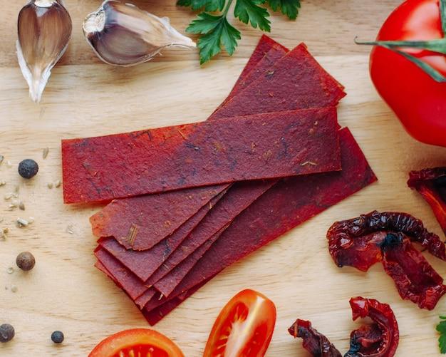 Fatias de tomate secas no papel na superfície de madeira. vista superior, configuração plana.