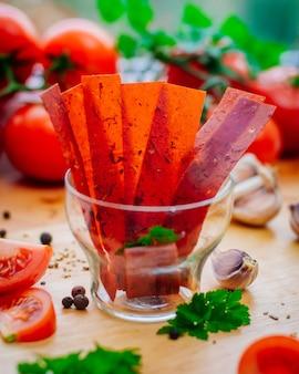 Fatias de tomate secas no vidro na superfície de madeira. foco seletivo.