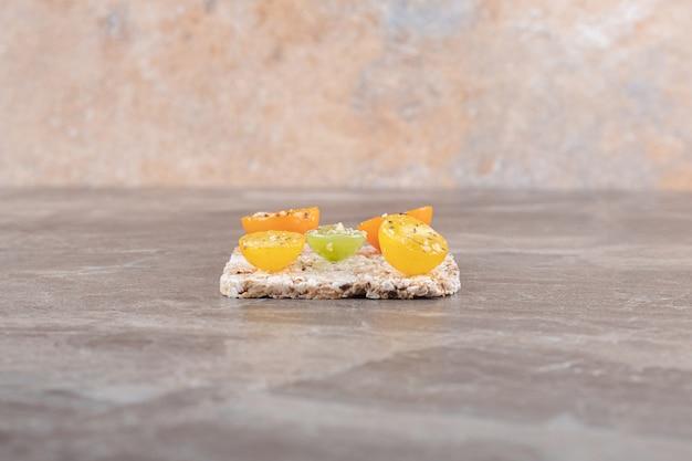 Fatias de tomate temperado com bolo de arroz por baixo, na superfície de mármore