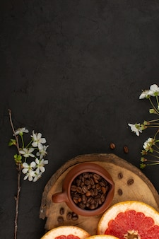 Fatias de toranja de vista superior, juntamente com sementes de café marrom no fundo escuro