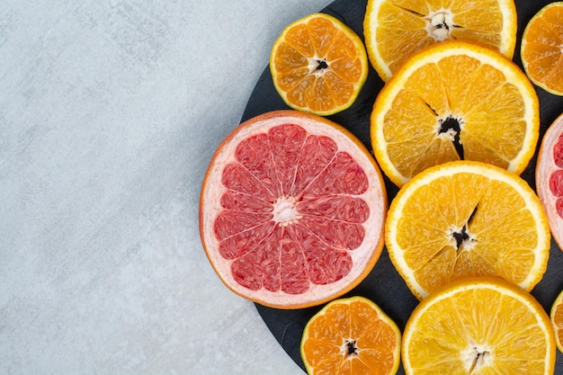 Fatias de toranja, laranja e tangerina no quadro negro. foto de alta qualidade