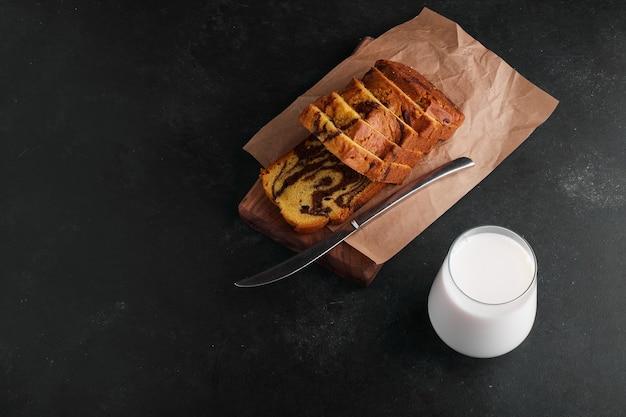 Fatias de torta de cacau em uma placa de madeira com um copo de leite.