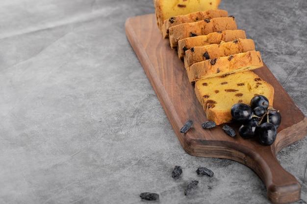 Fatias de torta de sultana em uma travessa de madeira com um cacho de uvas vermelhas.