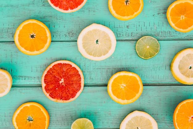 Fatias de várias frutas cítricas suculentas no topo da mesa de madeira