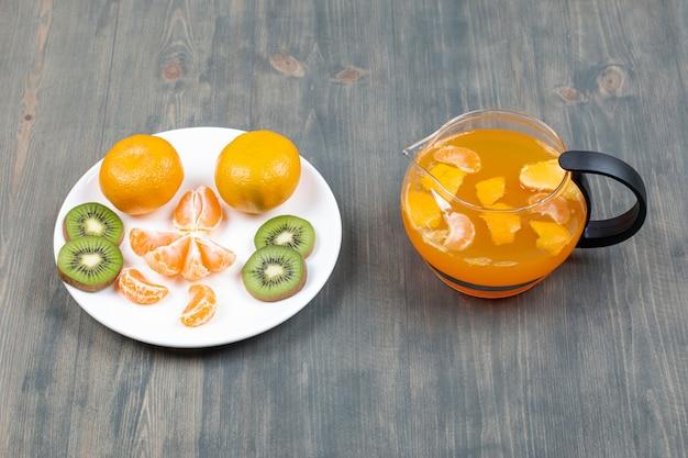 Fatias de várias frutas em uma jarra de vidro com suco