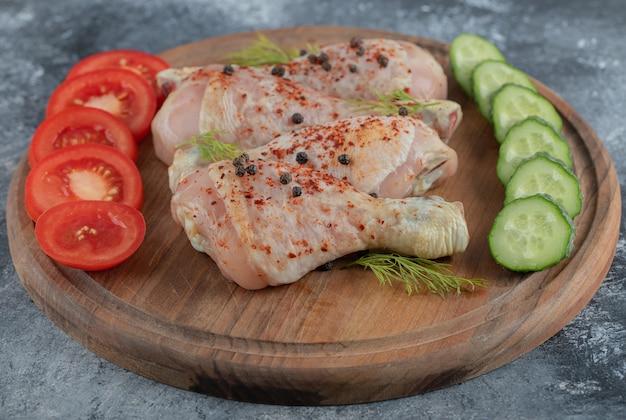 Fatias de vegetais frescos e pernas de frango cru.