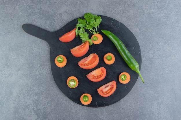 Fatias de vegetais maduros na placa de corte preta.