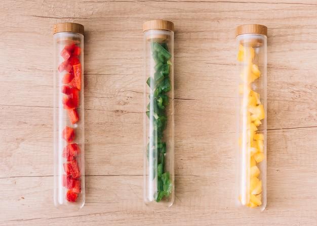 Fatias de vermelho; fatias de pimentão verde e amarelo no recipiente de tubos de ensaio transparente na mesa de madeira