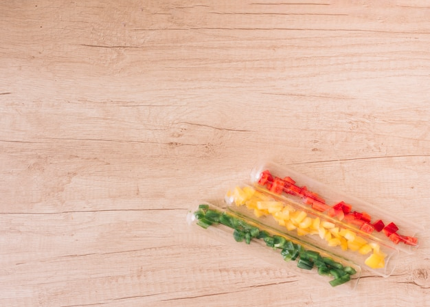 Fatias de vermelho; pimentão verde e amarelo dentro dos tubos de ensaio no canto da superfície de madeira