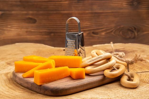 Fatias de vista frontal de bagels ovais ralador de caixa de queijo na tábua de cortar em chão de madeira