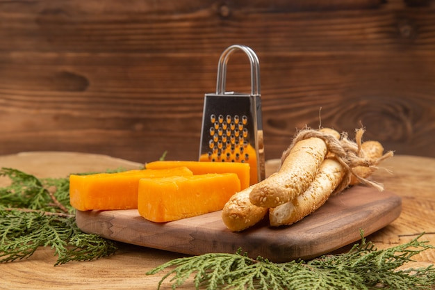Fatias de vista frontal de ralador de pão de queijo na tábua de cortar galhos de árvores de pinho na mesa de madeira