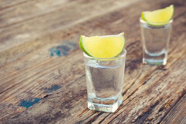 Fatias de vodka e limão na madeira