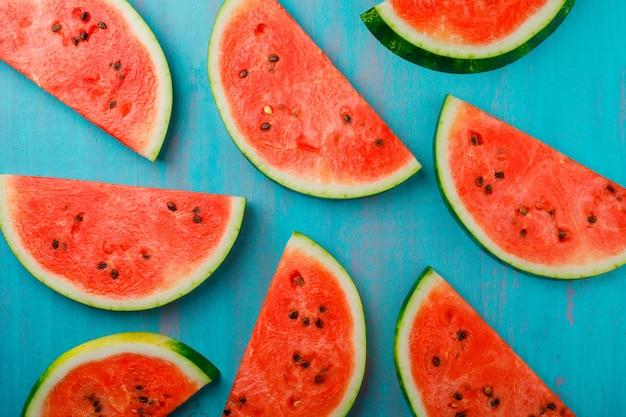 Fatias deliciosas da melancia no fundo azul, vista superior.