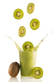 Fatias deliciosas e nutritivas de kiwi caindo em um copo de smoothie de kiwi fresco no fundo branco. bebida natural nutritiva para um estilo de vida saudável. bebida orgânica, vitamínica e desintoxicante.