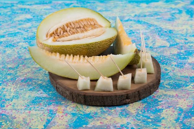 Fatias e cubos de melão em uma travessa de madeira.