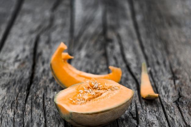Fatias e metade melão cantalupo sobre uma velha mesa resistiu