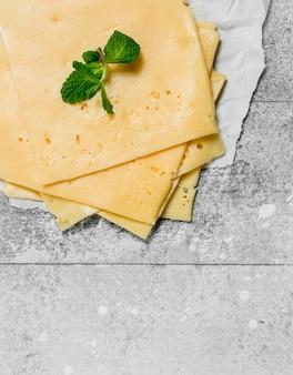 Fatias finas de queijo com um ramo de hortelã. sobre uma superfície rústica.