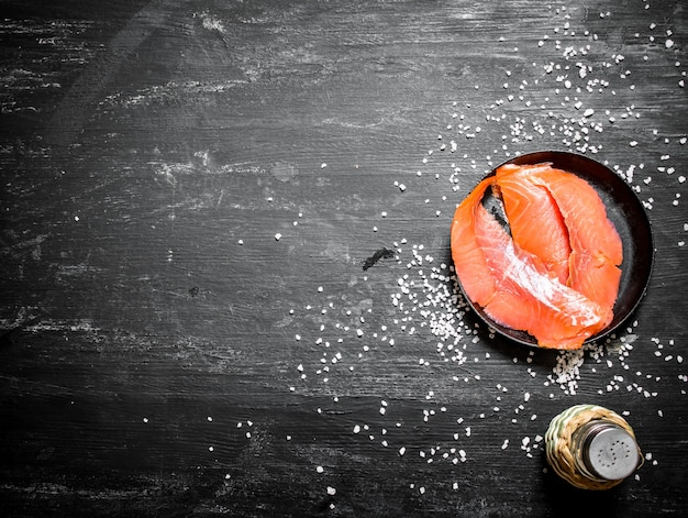 Fatias finas de salmão defumado com sal no quadro negro.