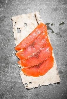 Fatias finas de salmão em tecido velho no concreto.