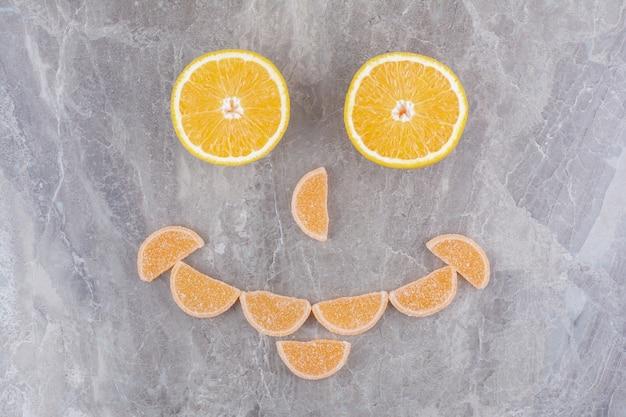 Fatias frescas de laranja com geleias em fundo de mármore.
