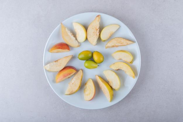 Fatias frescas de maçã e kumquats num prato, no mármore.