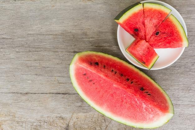 Fatias frescas de melancia em uma placa em um fundo de madeira
