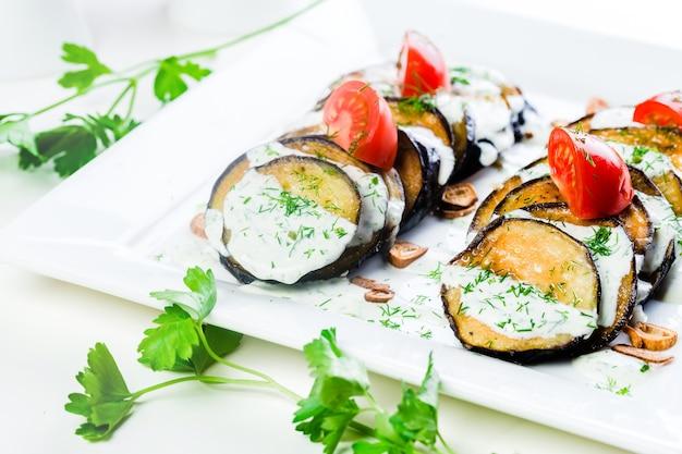 Fatias grelhadas de berinjela e tomate em pilha com molho picante
