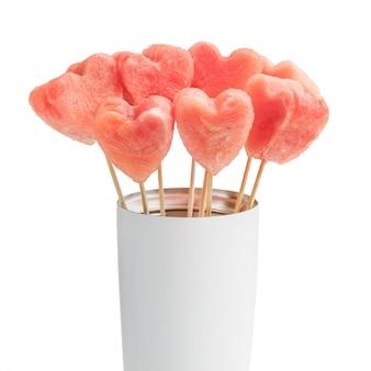 Fatias heart-shaped da melancia em varas de madeira na bacia branca.