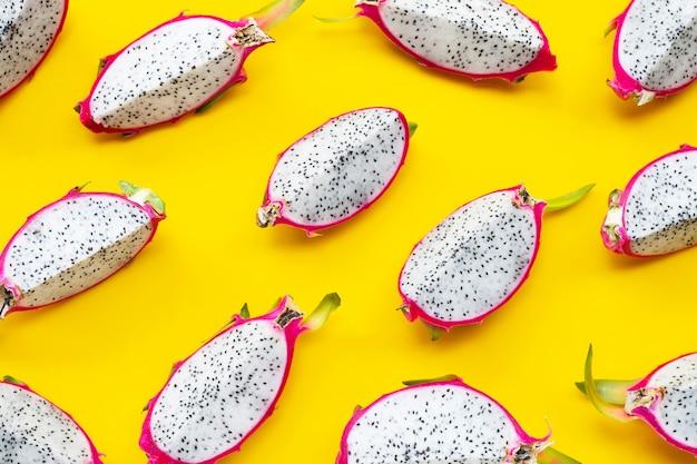 Fatias maduras de fruta-dragão ou pitaiaiás sobre fundo amarelo.