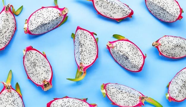 Fatias maduras de fruta-dragão ou pitaiaiás sobre fundo azul.