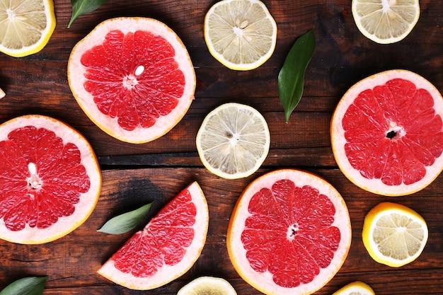 Fatias maduras de limão e toranja em fundo de madeira