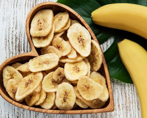 Fatias ou chips de banana caramelada em uma mesa de madeira branca