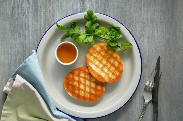 Fatias redondas grelhadas de queijo grego com mel, hortelã fresca e folhas de coentro. postura plana em madeira cinza claro