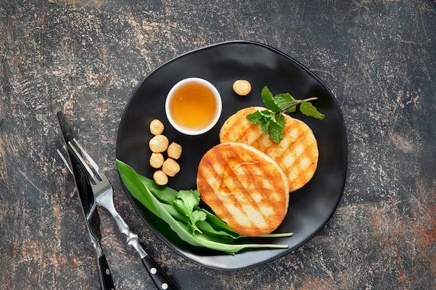 Fatias redondas grelhadas de queijo grego com mel, hortelã fresca e folhas de coentro. postura plana na mesa cinza escura