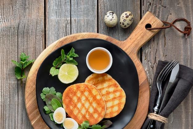 Fatias redondas grelhadas de queijo grego com mel, salada verde e ovo de codorna. postura plana em madeira rústica