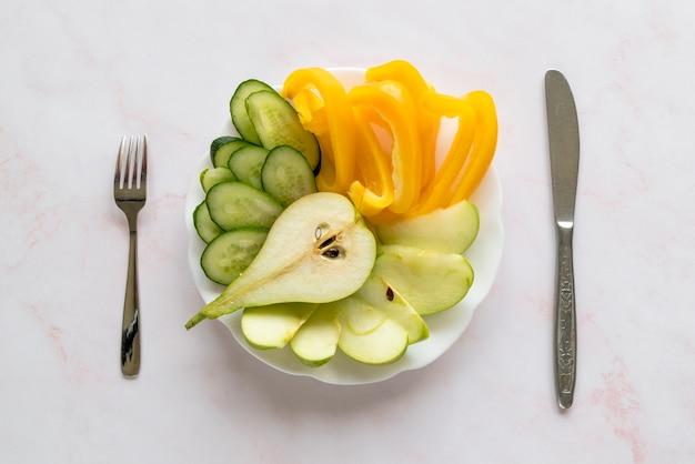 Fatias saudáveis de bellpepper; pepino; pêra no prato com garfo e faca de manteiga