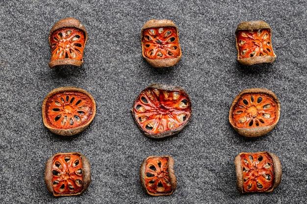 Fatias secas de matum do fruto do bael (marmelos de aegle) na bacia de madeira no fundo preto.