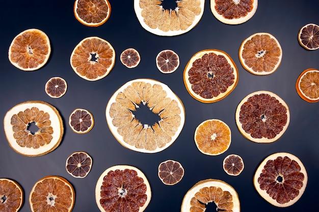 Fatias secas de várias frutas cítricas closeup no escuro